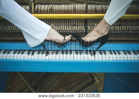 Legs On Piano Keyboard Blue Color, Fashion. Pop And Classical Music, Melody, Rhapsody. Piano And Sex