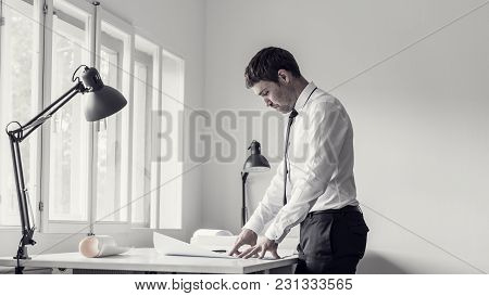 Retro Toned Image Of A Businessman Analyzing Plans While Working At His Desk In A Modern Office.