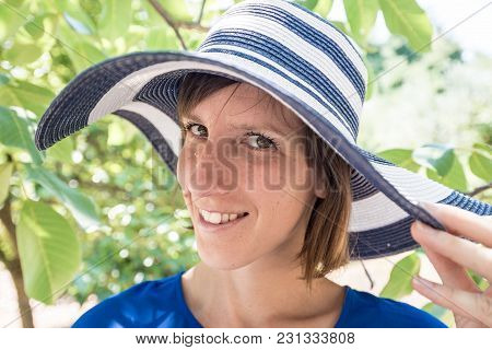 Smiling Woman In An Elegant Sunhat Holding The Wide Floppy Brim With Her Hand As She Stands Under Th