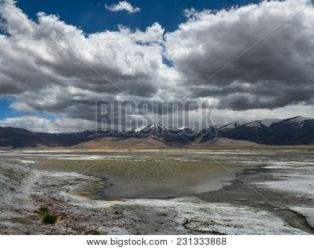 Salt Lake Among The High Mountains, Muddy Water Surface, White Coast, In The Background Of The Mount