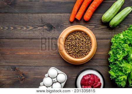 Dry Pet Food With Natural Ingredients. Raw Meat, Vegetables Zucchini And Carrot Near Eggs On Dark Wo