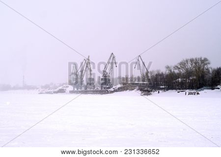 Cargo Port With Cranes On The Frozen Water Area During The Termination Of Navigation In Winter