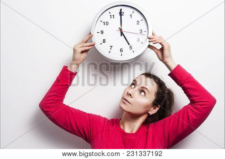 Watch The Time Concept. The Girl Is Holding Round Classic Watch Over Her Head. Young Brunette Woman
