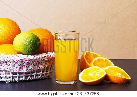 Fresh Orange Juice In Glass Beaker And Whole Oranges In Basket On A Table. Sliced Orange Slices And