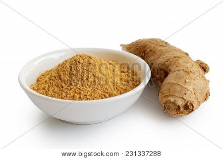 Finely Ground Dry Ginger In White Ceramic Bowl Isolated On White. Fresh Whole Root Ginger.