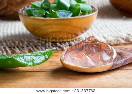 Aloe Vera Gel On A Spoon, With Pieces Of Aloe Vera Leaves In The Background