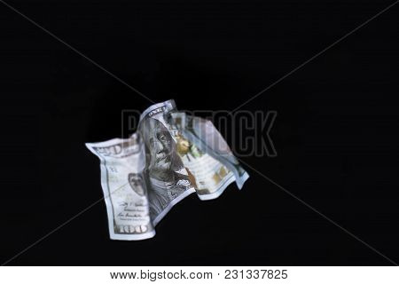 A Crumpled Dollar On The Black Background