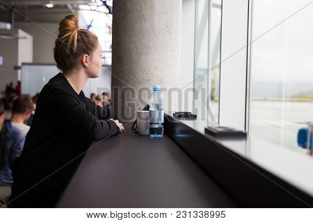 Rear View Of Mid Adult Traveling Woman Waiting At The Airport And Looking Through Window