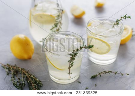 Homemade Summer Drink With Lemon, Thyme And Ice In The Glasses On The Table.