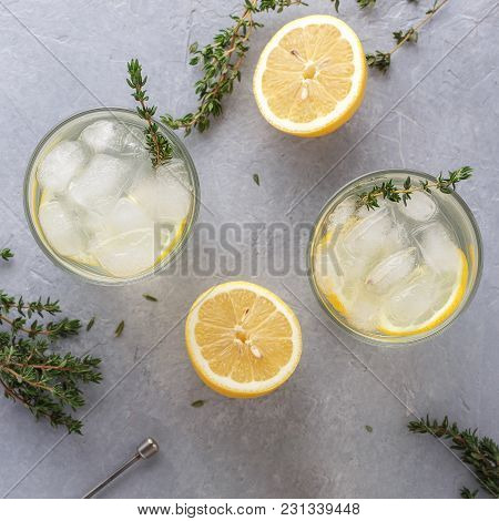 Cold Lemonade With Thyme In Two Glasses On The Gray Stone Background.