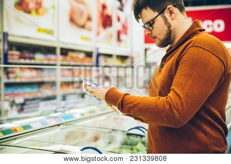 Man Read Info On Pack Of Beans In Store. Shopping Concept. Inside Grocery