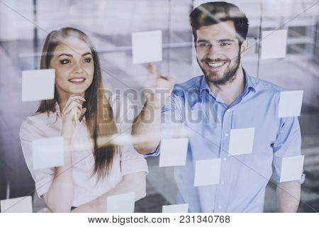 Young Businessman And Businesswoman Working On New Project With Many Sticky Notes On Glass Screen In