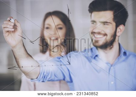 Young Businessman And Businesswoman  Drawing A Graph On Glass Screen In Office.