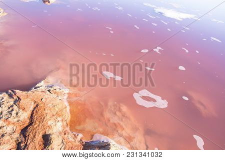 Beautiful Pink Salt Lake Laguna Scenery With Small Rocks Blue Purple Magenta Color Gradient. Bright