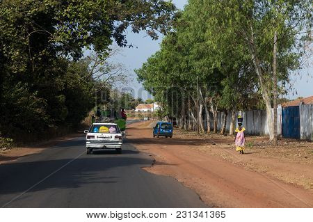 Bissau, Republic Of Guinea-bissau - January 28, 2018: Woman Walking Along A Road Carrying A Basket O