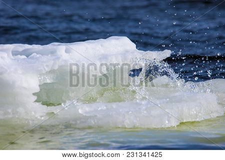 A Lump Of Ice Floats And Melts Along The River