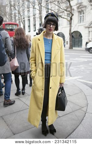 London - February 18: Brunette Woman In A Yelllow Coat   Outside Somerset House During London Fashio