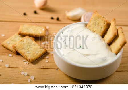 Salted Snacks With Pepper, Salt, Greens In White Sauce On Wooden Table