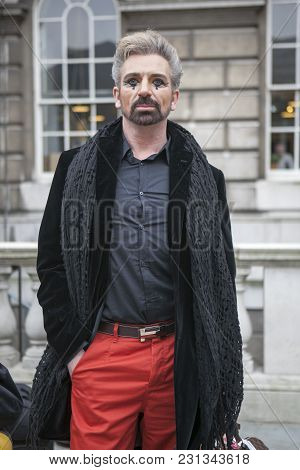 London - February 18: Man Models With Makeup Wearing Red Trousers  Poses For Photographers With Silv