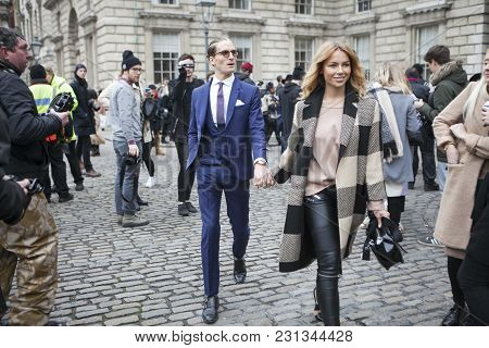 London - February 18: Blond Woman In Grey Coat With Man In Blue Suit Poses For Photographers With Si