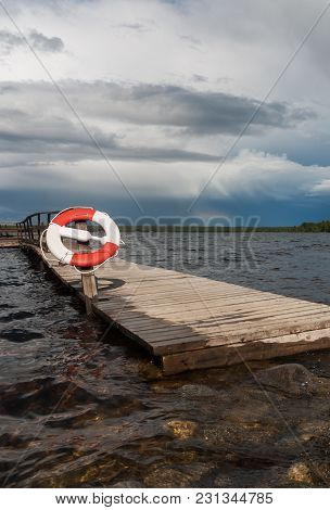 Wooden Pier With A Lifeline Against A Background Of Gray Clouds And A Rainbow