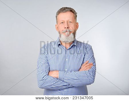 Senior man in casual clothes on grey background