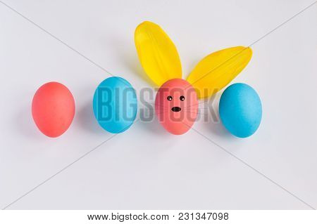 Happy Easter Concept. Big Colorful Eggs With Furry Bunny Ears Isolated On White Background. A Muzzle