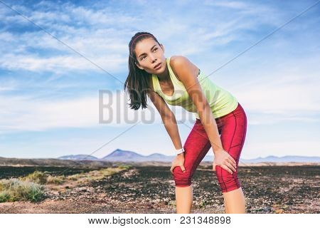 Tired runner girl taking a break breathing during jogging training workout outdoor on desert trail. Asian woman sweating in summer heat.