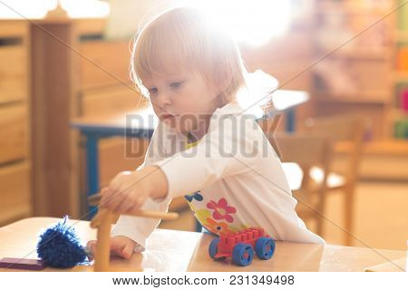 kid playing in kindergarten or day care centre with interest
