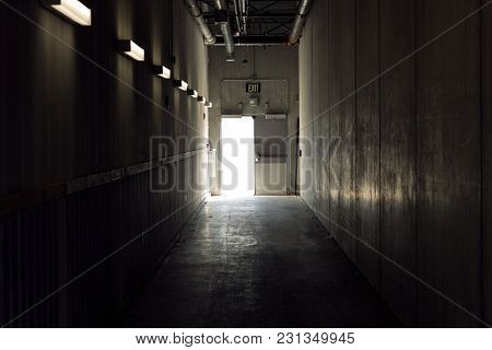 Technical Corridor With Light At The End. Exit Sign Above The Door.
