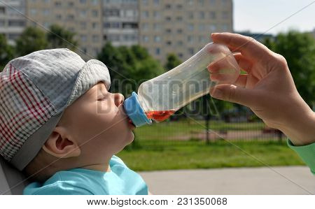 Head Of Tired Falling Asleep Baby And Hand Of His Mother Who Gives To Him  Drink   Juice From A Plas