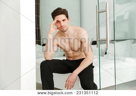 Portrait of a serious naked man sitting on bed in home looking camera.