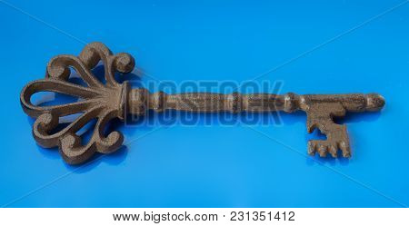 Isolated Metal Key On The Blue Background.