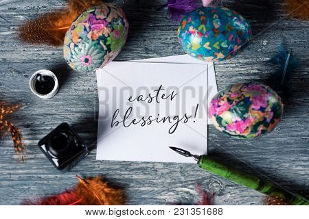 high angle view of a piece of paper with the text easter blessings, an ink bottle, a dip pen, some different homemade decorated eggs, made by myself, and some feathers, on a gray wooden table