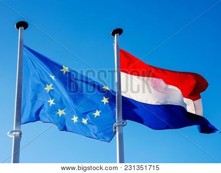closeup of a flag of the European Union and a flag of Luxembourg hanging in its respective poles, waving on the wind, against the blue sky