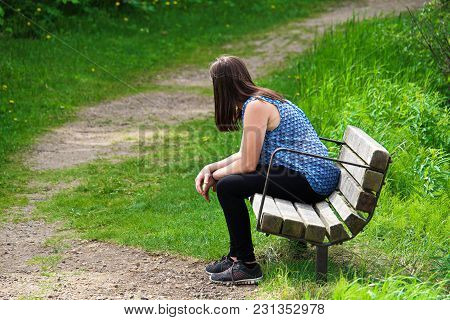 A Young Woman Rests On A Bench As A Trail Winds Around Her.