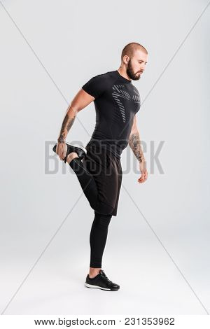 Photo of strong healthy young sportsman bodybuilder. Looking aside make sports exercises.