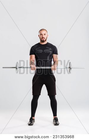 Full length picture of strong healthy young sportsman. Looking camera make sports exercises with barbell.