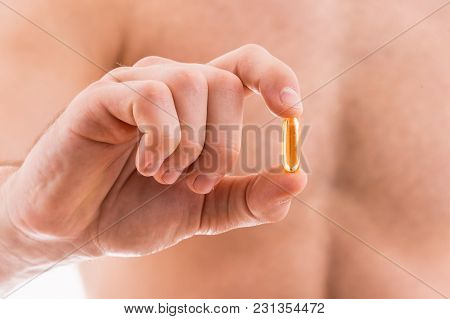 Young Man Holding Orange Pill Isolated On White Background.