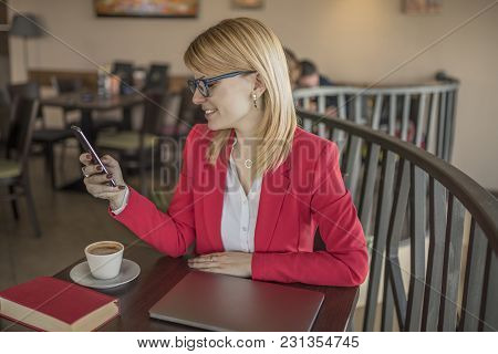 Young Blonde Woman Using Smart Phone, Texiting Message In Coffee Shop, Restaurant