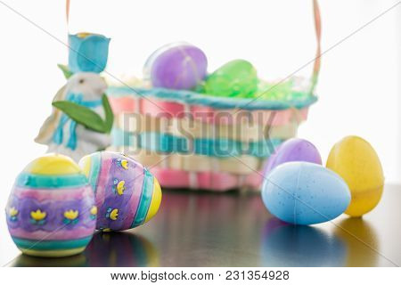 An Easter Bunny Is Set A Long Side His Basket Filled With Easter Eggs. Plastic And Decorated Ceramic