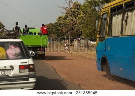 Bissau, Republic Of Guinea-bissau - January 28, 2018: Woman Walking Along A Road With An Old Car And