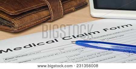 Medical Claim Form On A Wooden Surface. Near Leather Wallet, Fountain Pen Blue, Mobile Phone