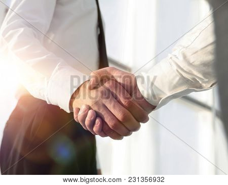 Closeup of a business handshake, on bright  background