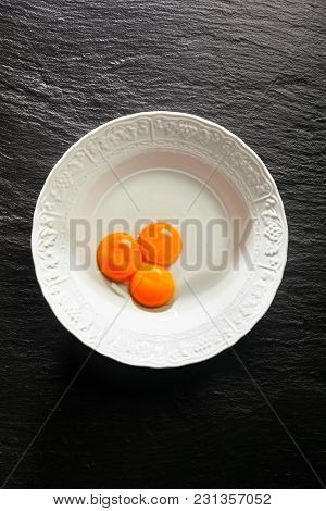 Yolks In A White Bowl On A Black Stone Background. Copy Space