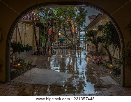 Arch In Ventura Harbor Village Shows Reflected Trees On Sidewalk Due To Early Morning Rain Storm On