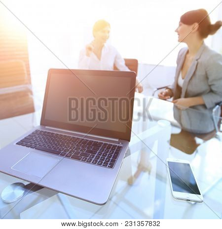 laptop and a smartphone on the desktop of a businessman