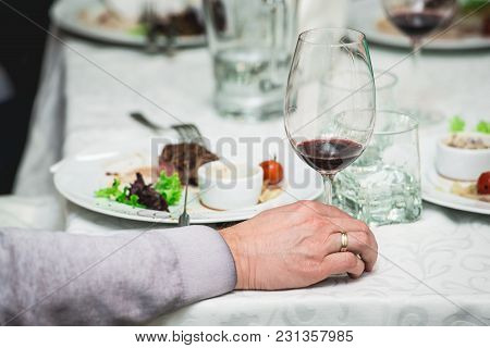 Mans Hand Holds A Glass Of Wine. Fresh Grilled Bbq Roast Beef Steak And Sauce On A White Plate With