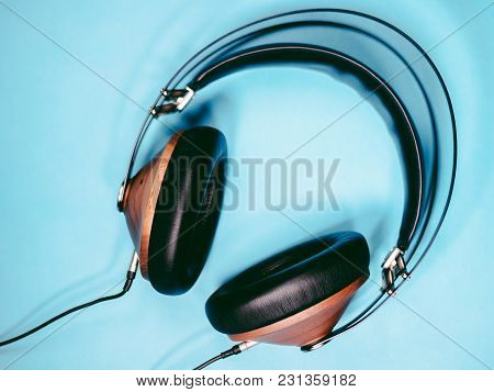 Black Wooden Headphones Audio For Listen Isolated On Blue Background