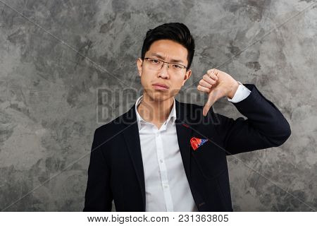 Portrait of an upset young asian man dressed in suit showing thumbs down gesture over gray background
